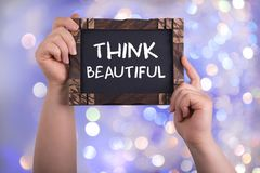 Think beautiful. A woman holding chalkboard with words think beautiful on bokeh light background stock photography