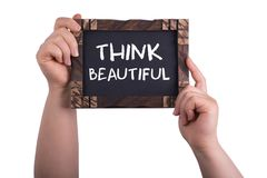 Think beautiful. A woman holding chalkboard with words think beautiful isolated on white background royalty free stock images