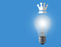 Think Big Concept. Light bulb and crown on blue background, business leadership stock photos