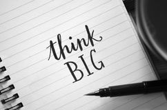 THINK BIG hand-lettered in notebook. With brush pen and cup of coffee on wooden desk Stock Photo