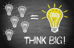 Think big. Illustration on a blackboard showing five small dim light bulbs beside a larger lit tungsten filament bulb with text 'think big!' in upper case white stock images