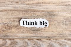 Think Big text on paper. Word Think Big on torn paper. Concept Image Stock Image