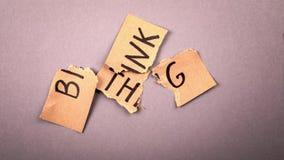 THINK BIG. Torn cardboard with an inscription on a grey background