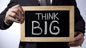 Think big written on blackboard, male in suit holding sign, motivational concept stock images