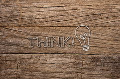 Think and bulb written on wooden background Stock Photos