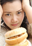 Think diet or eating. Image of woman thinking between diet or eating hamburger and sandwich royalty free stock photo