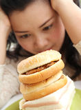 Think diet or eating. Image of woman thinking between diet or eating hamburger and sandwich Stock Image