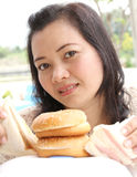Think diet or eating. Image of woman thinking between diet or eating hamburger and sandwich royalty free stock photography