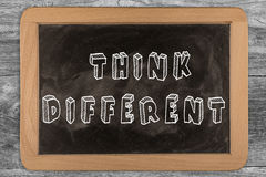 Think different - chalkboard with outlined text. On wood Stock Image