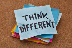 Think different concept. Motivational phrase on a stack of sticky notes against cork bulletin board stock images