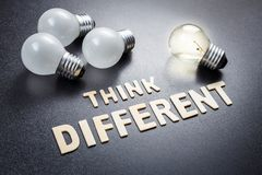 Think Different and Different Bulb. Think Different text by wood letters with unique light bulb glowing Stock Photography