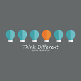 Think Different. One orange bulb with some blue bulbs on a gray background Stock Image