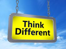 Think different on billboard. Think different yellow light box billboard on blue sky background Royalty Free Stock Photography