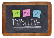 Think, do, be positive concept. Think, do, be positive - positivity concept, color sticky notes, white chalk and handwriting on a vintage slate blackboard Royalty Free Stock Photos