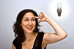 Think environment!. Smiling woman having a brilliant environmentally friendly thought and a compact fluorescent light bulb above her head stock image