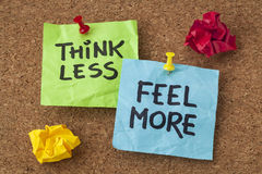 Think less, feel more advice. Think less, feel more - words of wisdom - handwriting on colorful sticky notes royalty free stock photo