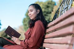 Cheerful international woman being deep in thoughts. Think about future. Kind longhaired girl looking aside and holding Holy Bible in both hands stock photo