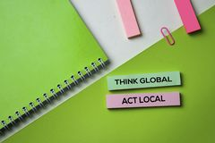 Think Global Act Local text on top view office desk table of Business workplace and business objects stock images