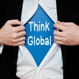 Think Global Concept. Man Showing a Superhero Suit Underneath His Shirt With a Message Text Written On It Royalty Free Stock Photography