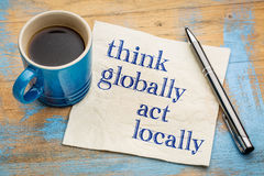 Think globally, act locally. Reminder - handwriting on a napkin with a cup of espresso coffee royalty free stock photo