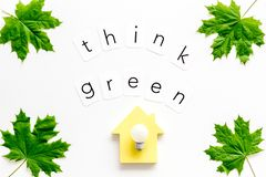 Think green concept with maple leave, house and lamp on white background top view. Eco friendly. Think green concept with maple leave, house and lamp on white stock photo