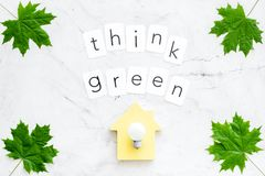 Think green concept with maple leaves, house and lamp on white marble background top view. Think green concept with maple leaves, house and lamp and copy on stock photos