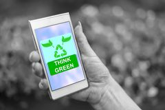 Think green concept on a smartphone. Female hand holding a smartphone with think green concept stock images
