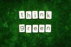 Think green copy for ecological concept on green texture background top view.  royalty free stock photography