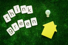 Think green copy and house with bulb for ecological concept on green texture background top view.  royalty free stock photos