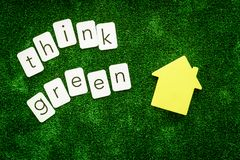 Think green copy and house for ecological concept on green texture background top view.  stock image