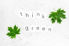 Think green copy with green maple leaves for ecology concept on marble background top view.  royalty free stock image