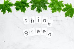 Think green copy with green maple leaves for ecology concept on marble background top view.  stock photos