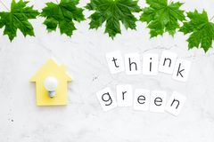 Think green copy with green maple leaves, house figure and lamp for ecology concept on marble background top view.  stock image