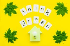 Think green copy with green maple leaves, house figure and lamp for ecology concept on yellow background top view.  royalty free stock images