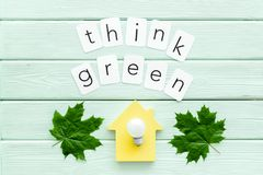 Think green copy with green maple leaves, house and lamp for ecology concept on mint green wooden background top view. Think green copy with green maple leaves royalty free stock image