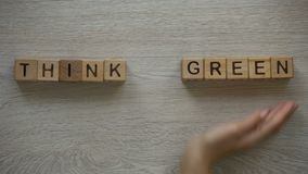 Think green phrase made by female hands, woman holding plant, ecofriendliness. Stock footage stock footage