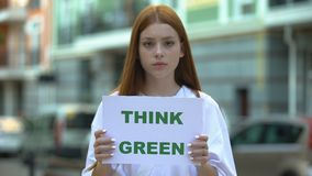 Think green sign in hands of girl, teenagers campaign against deforestation