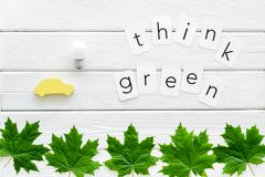 Think green text with car toy, lamp, green maple leaves on white wooden background top view. Ecology friendly. Think green text with car toy, lamp, green maple stock photo