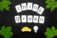 Think green text with car toy, lamp, green maple leaves on black background top view. Ecology friendly. Think green text with car toy, lamp, green maple leaves royalty free stock photo
