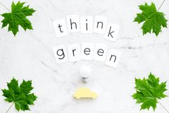 Think green text with car toy, lamp, green maple leaves on marble background top view. Ecology friendly. Think green text with car toy, lamp, green maple leaves stock images