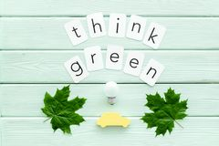 Think green text with car toy, lamp, green maple leaves on mint green wooden background top view. Ecology friendly. Think green text with car toy, lamp, green royalty free stock photos