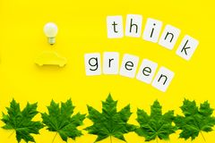 Think green text with car toy, lamp, green maple leaves on yellow background top view. Ecology friendly. Think green text with car toy, lamp, green maple leaves stock photography