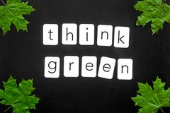 Think green text with green maple leaves on black background top view. Ecology friendly. Think green text with green maple leaves on black background top view stock photography