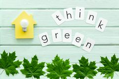 Think green text with house toy, lamp, green maple leaves on mint green wooden background top view. Ecology friendly. Think green text with house toy, lamp stock photo
