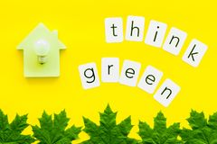 Think green text with house toy, lamp, green maple leaves on yellow background top view. Ecology friendly. Think green text with house toy, lamp, green maple stock photo