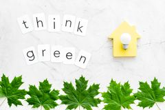 Think green text with house toy, lamp, green maple leaves on marble background top view. Ecology friendly. Think green text with house toy, lamp, green maple stock photography