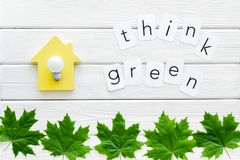 Think green text with house toy, lamp, green maple leaves on white wooden background top view. Ecology friendly. Think green text with house toy, lamp, green stock photos
