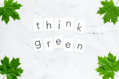 Think green text with green maple leaves on marble background top view. Ecology friendly. Think green text with green maple leaves on marble background top view stock photos
