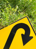 Think green - U-turn roadsign in lush vegetation Royalty Free Stock Photo
