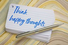Think happy thoughts. Reminder - handwriting on a stack of index cards against wavy marbled paper stock photos